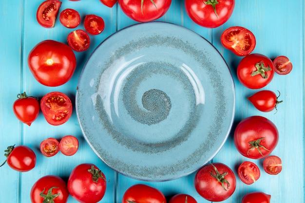 Bovenaanzicht van gesneden en hele tomaten rond plaat op blauw Gratis Foto