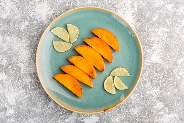 Bovenaanzicht van gesneden verse perziken binnen plaat met gesneden citroenen op het licht witte oppervlak Gratis Foto