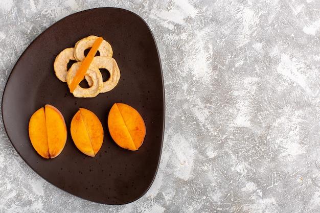 Bovenaanzicht van gesneden verse perziken in plaat met ananasringen op het licht witte oppervlak Gratis Foto