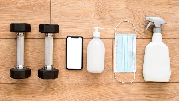 Bovenaanzicht van gewichten met reinigingsoplossing en smartphone voor sportschool Gratis Foto