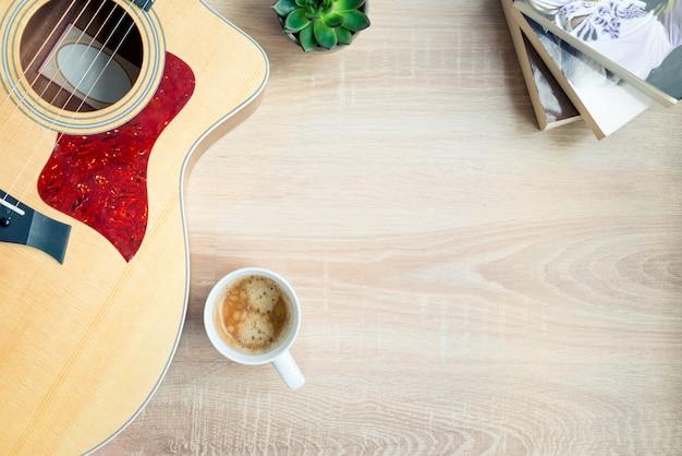 Bovenaanzicht van gezellige thuisscène. gitaar, boeken, kopje koffie, telefoon en vetplanten over hout. kopieer ruimte, mock-up. Premium Foto