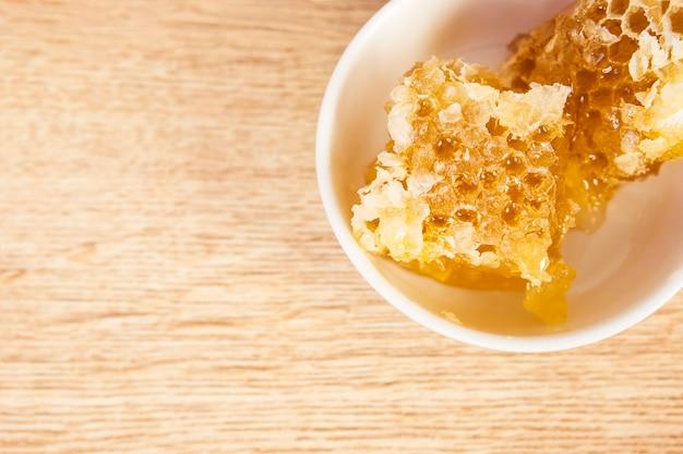 Bovenaanzicht van gezonde honingraat in kom op houten tafel Gratis Foto