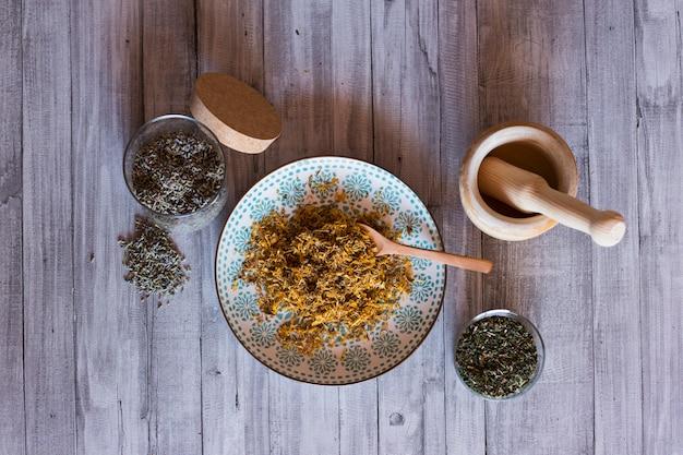 Bovenaanzicht van gezonde ingrediënten op tafel, houten mortel, gele kurkuma, lavendel en groene natuurlijke bladeren. overdag dichten Premium Foto