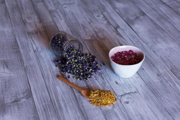 Bovenaanzicht van gezonde ingrediënten op tafel, rozen in een kom, gele kurkuma en lavendel natuurlijke bladeren. overdag dichten Premium Foto