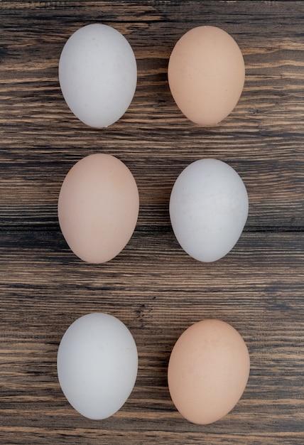 Bovenaanzicht van gezonde kippeneieren gerangschikt in een lijn op een houten achtergrond Gratis Foto