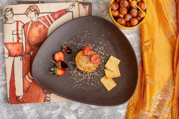 Bovenaanzicht van gezouten chips ontworpen met aardbeien in plaat op de witte tafel, chips snack fruitbes Gratis Foto