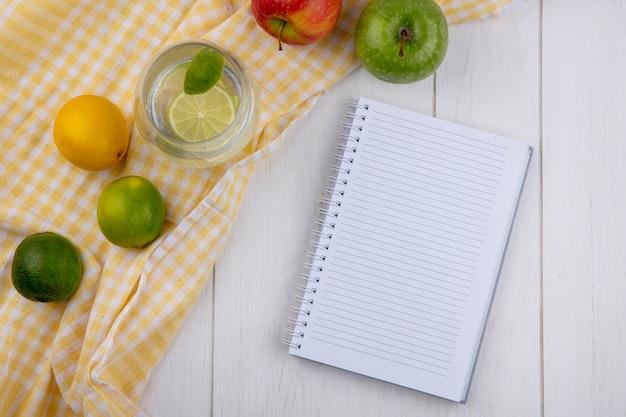 Bovenaanzicht van glas water met limoen en citroen op een gele geruite handdoek met een notitieblok op een wit oppervlak Gratis Foto