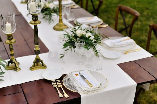 Bovenaanzicht van glaswerk en bestek op de houten tafel buiten, met witte eustomas en ruscus boeketten Gratis Foto