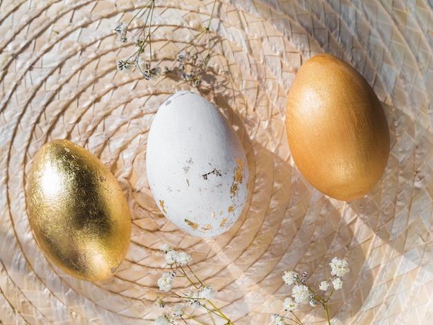 Bovenaanzicht van gouden gekleurde paaseieren op placemat Gratis Foto