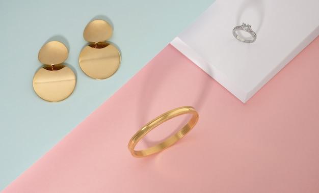 Bovenaanzicht van gouden jewelries op roze witte en groene achtergrond Premium Foto