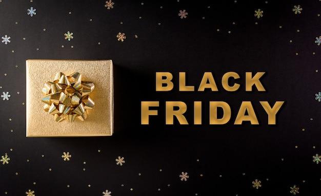 Bovenaanzicht van gouden kerst geschenkdozen op zwarte achtergrond met black friday-tekst Premium Foto