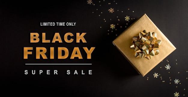 Bovenaanzicht van gouden kerst geschenkdozen op zwarte ondergrond met black friday-tekst Premium Foto