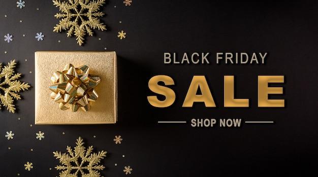 Bovenaanzicht van gouden kerstdozen en sneeuwvlok op zwarte achtergrond met zwarte vrijdag verkoop tekst Premium Foto
