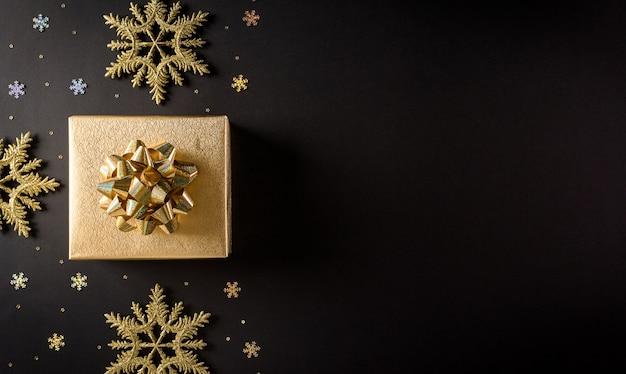 Bovenaanzicht van gouden kerstdozen en sneeuwvlok op zwarte muur met kopie ruimte voor tekst Premium Foto