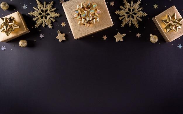 Bovenaanzicht van gouden kerstdozen en sneeuwvlok op zwarte muur, Premium Foto