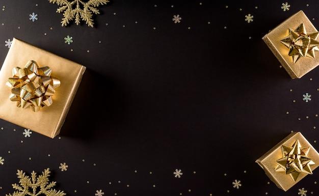 Bovenaanzicht van gouden kerstdozen op zwarte achtergrond met kopie ruimte voor tekst Premium Foto
