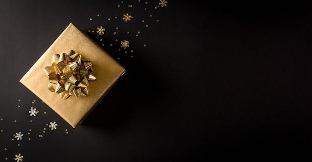 Bovenaanzicht van gouden kerstdozen op zwarte achtergrond Premium Foto