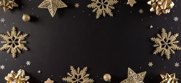Bovenaanzicht van gouden sneeuwvlok, sterren en kerstbal op zwarte muur met kopie ruimte Premium Foto