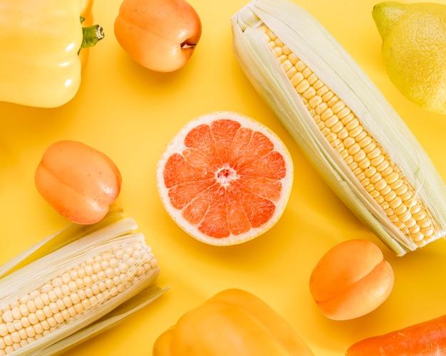 Bovenaanzicht van grapefruit met maïs en perziken Gratis Foto