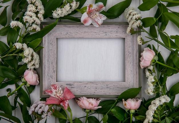 Bovenaanzicht van grijs frame met bladtakken en lichtroze bloemen op een grijze ondergrond Gratis Foto