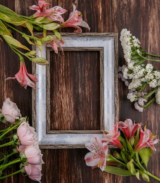 Bovenaanzicht van grijs frame met bloemen rond de randen op een houten oppervlak Gratis Foto