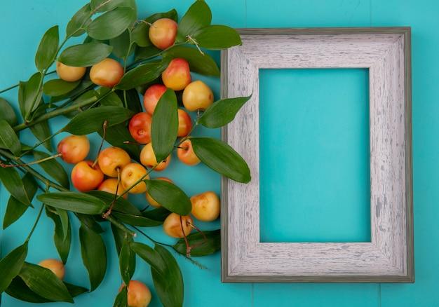 Bovenaanzicht van grijs frame met witte zoete kersen met bladtakken op een turkoois oppervlak Gratis Foto