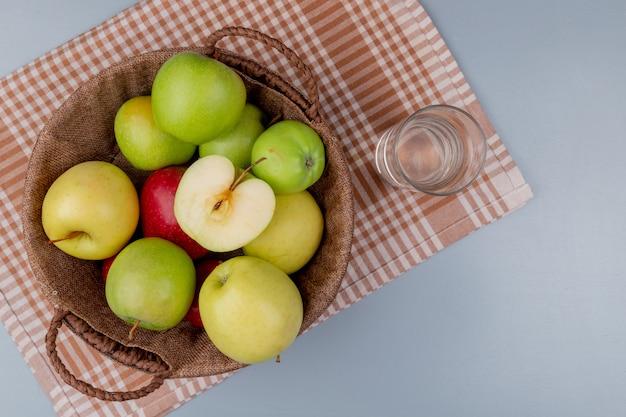 Bovenaanzicht van groen geel rode appels in mand en glas water op plaid doek en grijze achtergrond Gratis Foto
