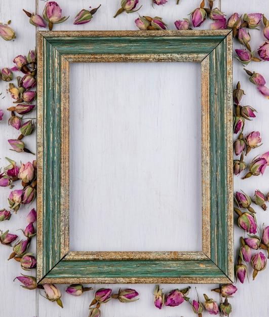 Bovenaanzicht van groenachtig gouden frame met gedroogde paarse rosebuds op een wit oppervlak Gratis Foto