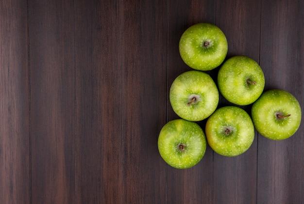 Bovenaanzicht van groene en verse appels gerangschikt in de vorm van een piramide in een houten oppervlak Gratis Foto
