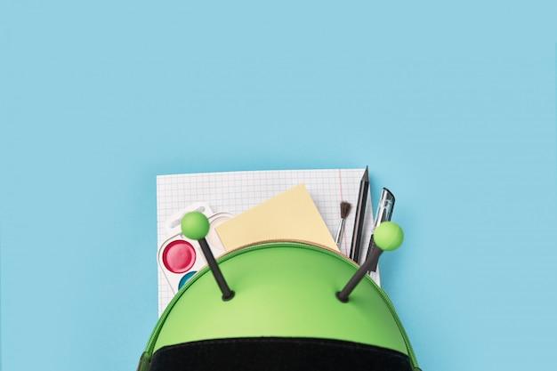 Bovenaanzicht van groene rugzak met school briefpapier. kleuterschool terug naar school Premium Foto
