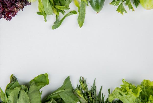 Bovenaanzicht van groenten als spinazie munt basilicum komkommer sla op witte ondergrond met kopie ruimte Gratis Foto
