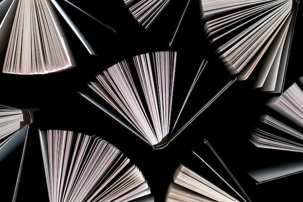 Bovenaanzicht van half geopende boeken op zwart Premium Foto