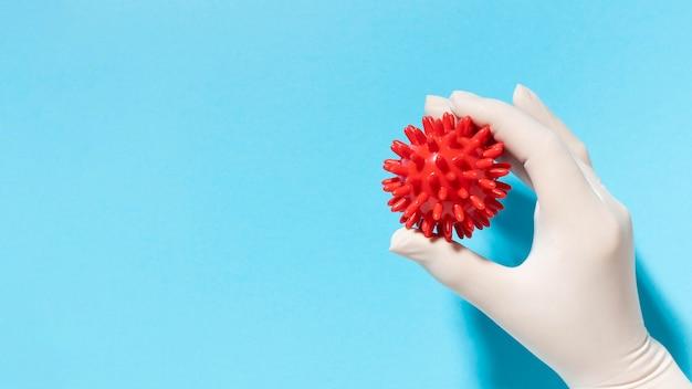 Bovenaanzicht van hand met handschoen met virus met kopie ruimte Gratis Foto