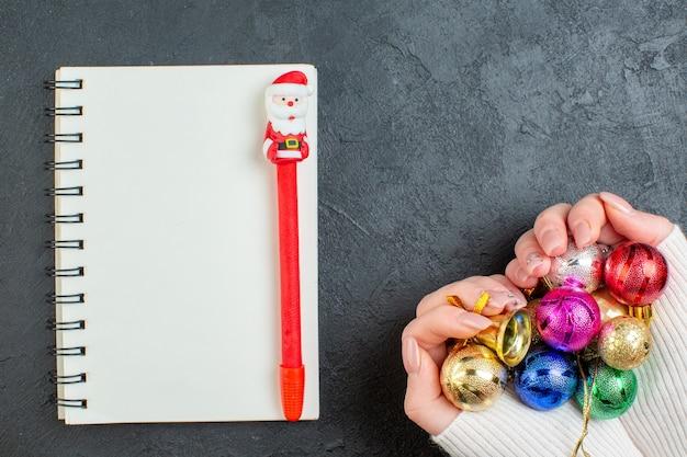 Bovenaanzicht van hand met kleurrijke decoratie accessoires notebook met pen op donkere achtergrond Gratis Foto