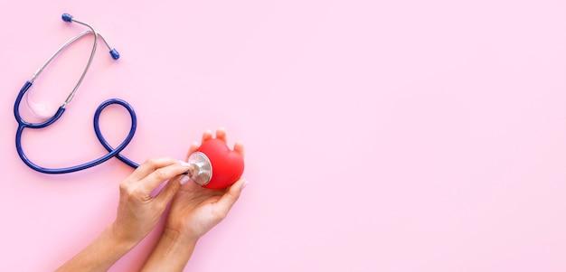 Bovenaanzicht van handen hartvorm controleren met een stethoscoop en kopieer de ruimte Premium Foto