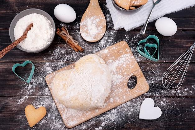 Bovenaanzicht van hartvormig deeg met keukengerei Gratis Foto