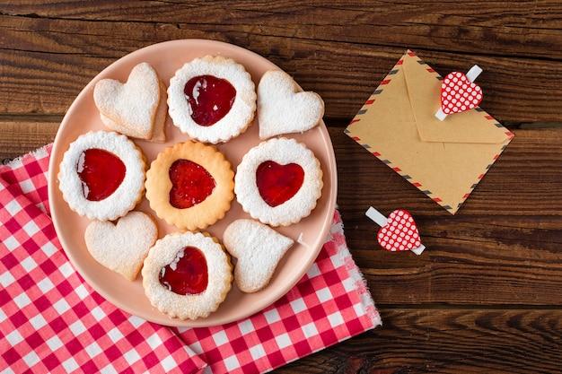 Bovenaanzicht van hartvormige koekjes op plaat met jam Gratis Foto