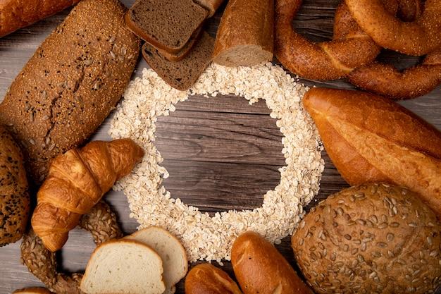 Bovenaanzicht van havervlokken in cirkelvorm en brood rond als baguette rogge witte cob bagel op houten achtergrond met kopie ruimte Gratis Foto