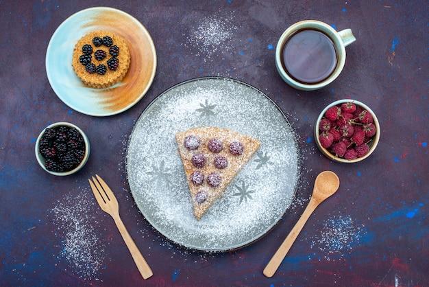 Bovenaanzicht van heerlijke cake met frambozen en thee op het donkere oppervlak Gratis Foto