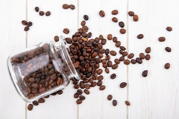Bovenaanzicht van heerlijke koffiebonen vallen uit een glazen pot op een witte houten achtergrond Gratis Foto