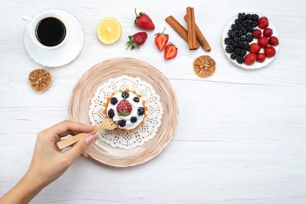 Bovenaanzicht van heerlijke romige cake met bessen eten krijgen door vrouw met kaneelkoffie op licht bureau, zoete cake Gratis Foto