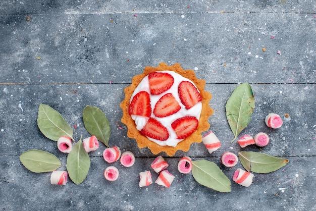 Bovenaanzicht van heerlijke romige cake met gesneden verse aardbeien en gesneden roze snoepjes op grijs, cake zoet bakroom fruit snoep Gratis Foto