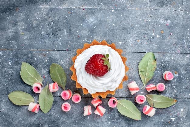 Bovenaanzicht van heerlijke romige cake met verse aardbeien en gesneden roze snoepjes op grijs, zoete cake bak room fruit snoep Gratis Foto