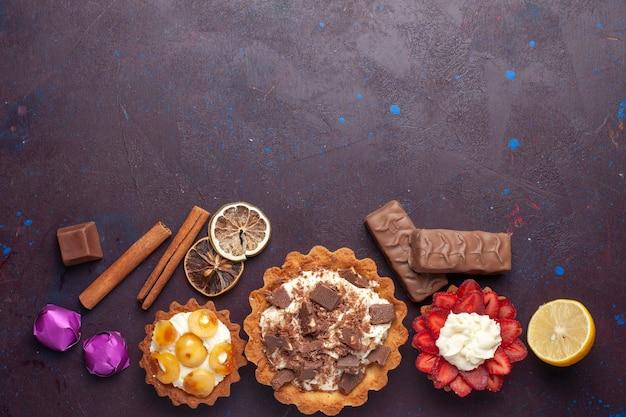 Bovenaanzicht van heerlijke taarten samen met kaneel en snoep op het donkere oppervlak Gratis Foto