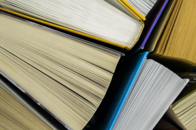 Bovenaanzicht van heldere kleurrijke hardback boeken in een cirkel. open boek, gewaaide pagina's. Premium Foto