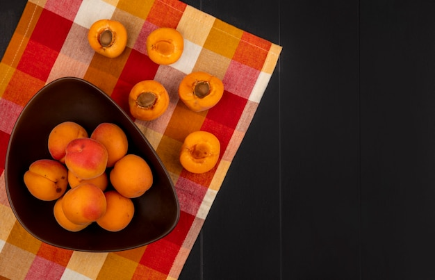 Bovenaanzicht van hele abrikozen in kom en patroon van half gesneden degenen op geruite doek en zwarte achtergrond met kopie ruimte Gratis Foto