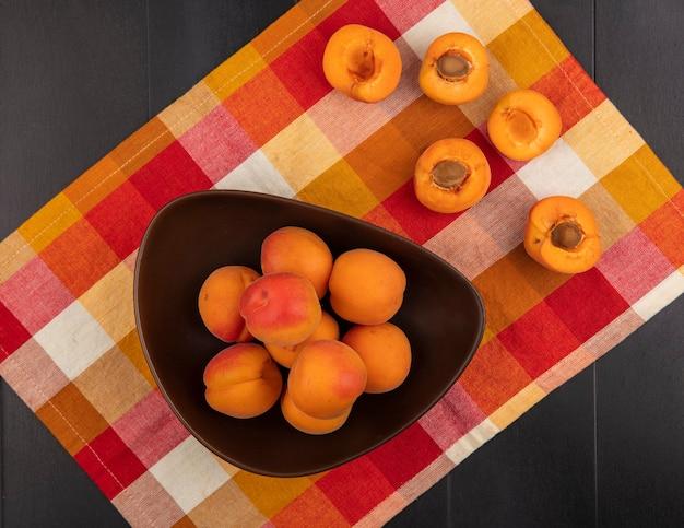 Bovenaanzicht van hele abrikozen in kom en patroon van half gesneden degenen op geruite doek en zwarte achtergrond Gratis Foto