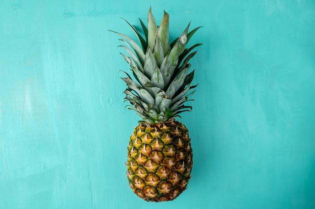 Bovenaanzicht van hele ananas op blauw oppervlak Gratis Foto