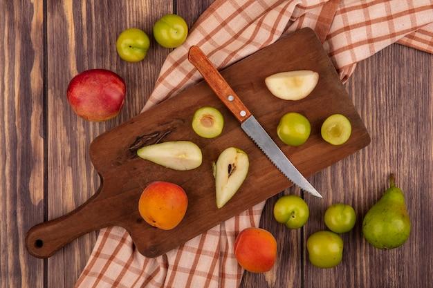 Bovenaanzicht van hele en gesneden fruit als abrikozenpeer pruim met mes op snijplank op geruite doek en patroon van perzik pruim peer abrikoos op houten achtergrond Gratis Foto