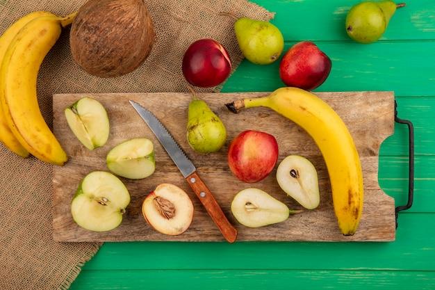 Bovenaanzicht van hele en halve gesneden fruit als peer, appel, perzik, banaan met mes op snijplank en kokos banaan op zak en groene achtergrond Gratis Foto